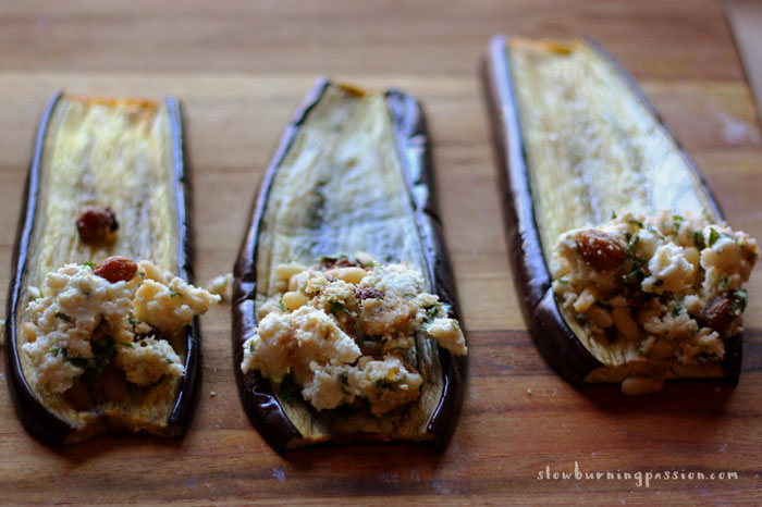 Eggplant Involtini is an Italian vegetarian classic. Roasted slabs of eggplant are rolled around a filling of cheese, toasted pine nuts, and raisins and baked in an Italian red gravy. Here the roasted eggplant is ready to be rolled around the filling.