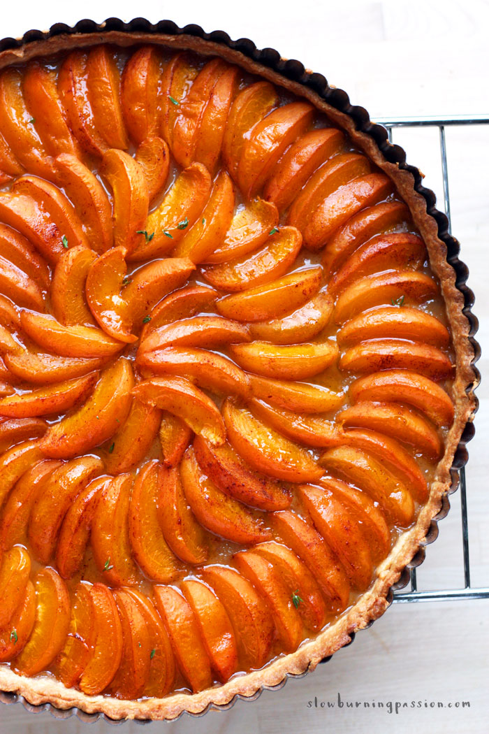 Freshly baked apricot tart cooling on a rack.