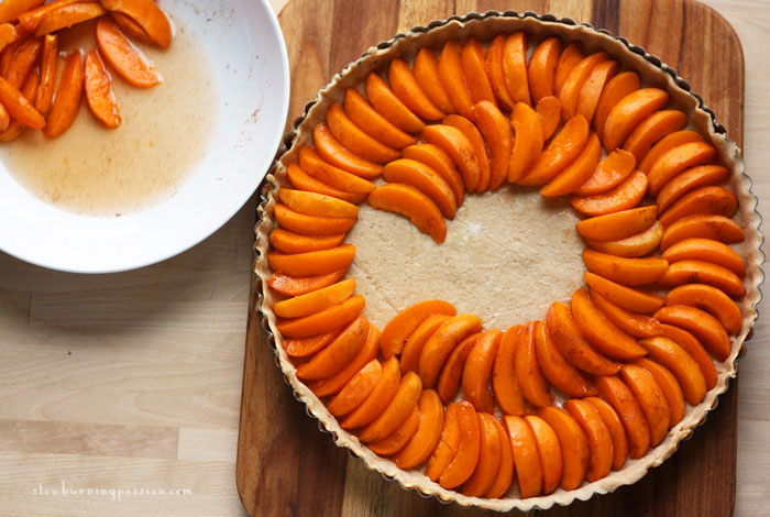 Arranging apricot slices on the whole wheat tart crust.